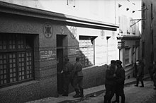 Photograph of a synagogue used as a brothel. Three German soldiers can been seen entering it.