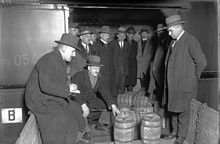 men standing around looking at barrels