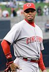 "A man in a grey baseball uniform with red sleeves and a red hat with a white ""C"" on it."