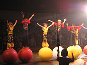 Five children in bright red and yellow costumes balance atop red and yellow spheres.