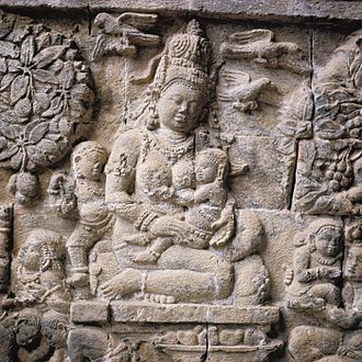 Hariti - The bas-relief of Hariti with her children on inner northern wall of Mendut, 9th century.