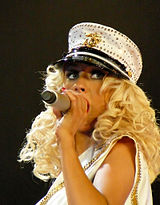A blonde woman performing on a microphone