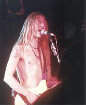 A male singer and guitarist, Jerry Cantrell, pictured onstage at a concert. He has an electric guitar strapped over his shoulder and he is singing into a microphone. He has long hair and he is not wearing any shirt.
