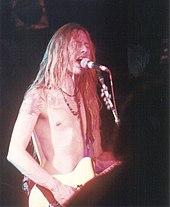 Um cantor e guitarrista, Jerry Cantrell, retratado no palco em um concerto.  Ele tem uma guitarra elétrica amarrado por cima do ombro e ele está cantando em um microfone.  Ele tem cabelo comprido e ele não está vestindo qualquer camisa.