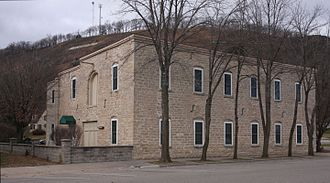 """Rushford, Minnesota - Rushford Wagon and Carriage Company, now an apartment building, with """"Rushford"""" on the side of the bluff behind it."""