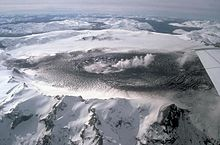 Glaciers around a black caldera from which steam is rising