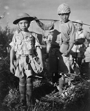 Slavery - A Chinese Nationalist soldier, age 10, member of a Chinese division from the X, boarding planes in Burma bound for China, May 1944.