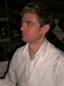A Caucasian male with dirty blond hair in a white suit.