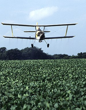 Agricultural aircraft - A Grumman Ag Cat applies a low-insecticide bait on a soybean field.