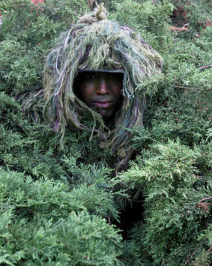Long-range surveillance - A soldier from Echo Company, 51st Infantry Company, Long-Range Surveillance, V Corps demonstrating a ghillie suit in 2004