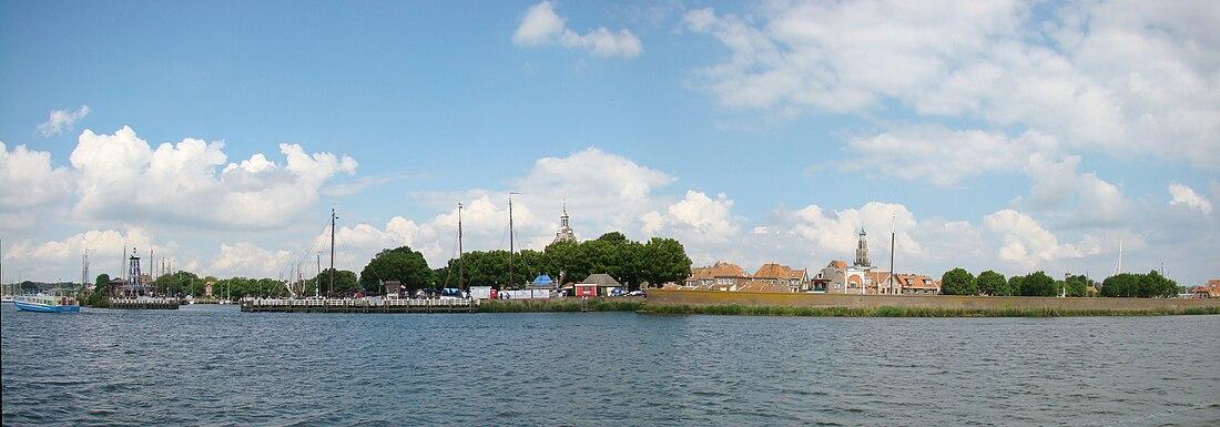 Panorama uitzicht op Enkhuizen vanaf het IJsselmeer. De kerktoren rechts van het midden is die van de Zuiderkerk, middenin de Drommedaris, op de voorgrond rechts zien we de Zeemuur en links de oude haven met 't Vuurtje.