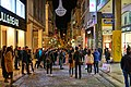 Ermou Street in the evening. In the distance the Byzantine Church of Panagia Kapnikarea.jpg