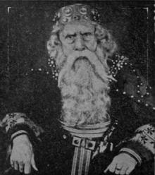 Portrait of a seated man dressed as King Lear. He has long white beard and wears a large crown.