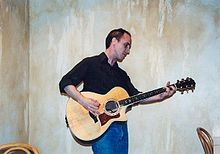 Johnston stands and plays acoustic guitar in the corner of a room.