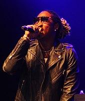 Un retrato de un hombre afroamericano con rastas, actuando en el escenario, vestido con una chaqueta y gafas de sol.