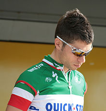 A man in his mid twenties wearing a cycling jersey bearing green, white, and red stripes. He wears sunglasses, and is looking downward.