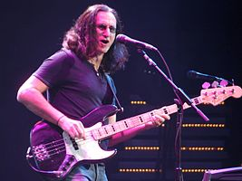 Geddy Lee playing his Fender Jazz Bass and singing at a 2008 live performance at the Xcel Energy Center