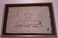 A white flag, with a five-pointed-star over the outline of a small cannon, with the words Come and Take It below.  The left corner of the flag has been torn off and sewn back on.