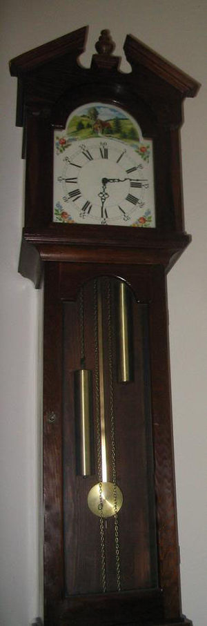 Longcase clock - Most of a longcase clock's height is used to hold the long pendulum and weights. The two chains attached to the weights and the lack of winding holes in the dial show this to be a 30-hour clock.