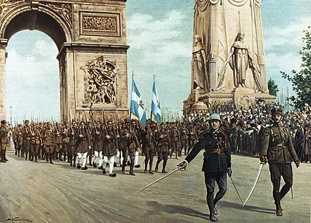 Paris Victory Parade of 14 July 1919 and the temporary catafalque (right) by the Arc de Triomphe (left). Greek Parade Paris 1919.jpg