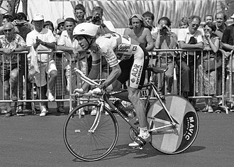 Individual time trial - Greg LeMond holding low-profile 'bullhorn' handlebars, with tri-bars in between his arms, at the 1989 Tour de France.