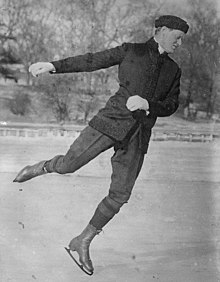 Man in his 30s, wearing dark trousers and coat, skating on an outdoor rink, facing to the right and looking downward towards the ice