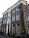 foto van Huis met deftige lijstgevel op voet van natuursteen met zwartgeverfde banden en aan weerszijden afgezet door natuurstenen blokpilasters