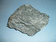 Komatiite sample collected near Englehart, Ontario, Canada.  Specimen is 9 cm wide.  Bladed olivine crystals are visible, though spinifex texture is weak or absent in this sample.