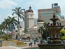 Street scene; a large fountain visible in the right foreground, a row of palm trees stretching away to the left, and in the centre of the image, across the street, a large white and beige stone building, with a tall domed central tower and two smaller domed towers to the right and left.