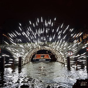 Boat going through tunnel surrounded by lughts