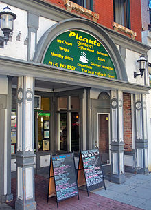"An ornate storefront with a semicircular green entablature over the entrance that says ""Picante"" in large letters and ""Quimbaya's Coffee House"" in smaller letters below it, surrounded by the names of some foods and drinks"