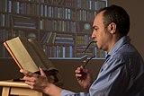 Leyendo un libro sustentado por un atril.jpg