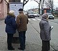 Ludzie czytający klapsydry. Tablica ogłoszeń przy wjeściu na największe tomaszowskie targowisko na placu Narutowicza.jpg