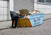 A man rummaging through a skip at the back of an office building in Central London