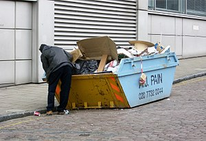 Dumpster diving - A man rummaging through a skip at the back of an office building in Central London