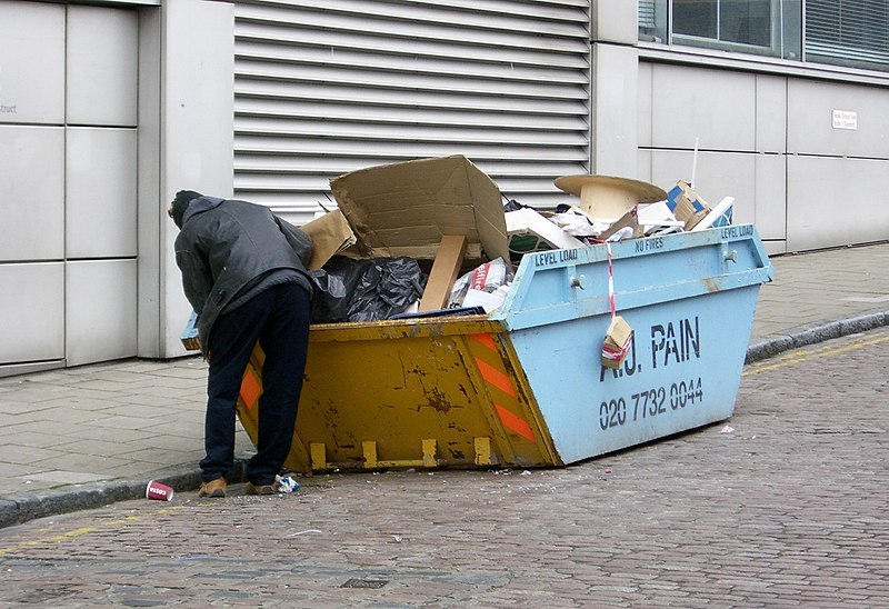 File:Man rummaging thought a skip.jpg
