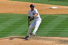 Mariano Rivera in a white pinstriped baseball uniform and navy blue cap stands on a dirt mound. He is striding forward to the right as he clutches a baseball.
