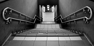 "Stairs - A straight stairway with tiled treads, a double railing and two landings in the ""Porta Garibaldi"" station, Milan"