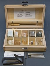 Open wooden box with ten compartments, each containing a numbered mineral specimen.