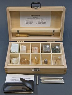 Open wooden box collection containing ten compartments, each holding a numbered mineral specimen.