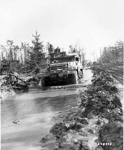 Ein amerikanisches Halbkettenfahrzeug bahnt sich den Weg durch die schlammigen Straßen des Hürtgenwalds