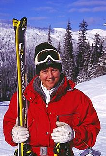 A smiling female skier wears a red winter jacket, white gloves, and white goggles over of a black winter cap. She holds a pair of skis in her right hand and a pair of ski sticks in her left hand. Behind her, a snowy pine-covered landscape.