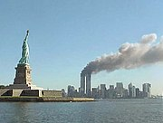 The World Trade Center on fire with the Statue of Liberty in the foreground