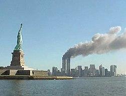 WTC en llamas el 11-S con la Estatua de la Libertad en primer plano