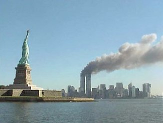 11 september 2001, Frihetsgudinnan med det brinnande World Trade Center i bakgrunden.