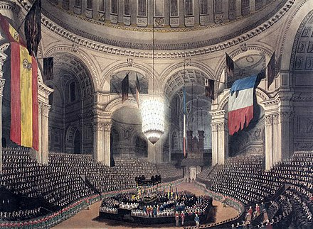 Nelson's coffin in the crossing of St Paul's during the funeral service, with the dome hung with captured French and Spanish flags NelsonTomb.jpg