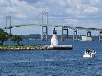 Goat Island (Rhode Island) - Newport Harbor Light (1842) on northern tip of Goat Island as seen from Easton's Point. The Claiborne Pell Bridge can be seen in the background.