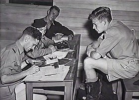 Three men writing at desks, while another man supervises