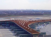 Overhead view of airport terminal, with planes at the gate and on the tarmac
