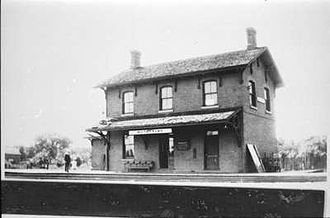 """Port Whitby and Port Perry Railway - The Uptown Station (placarded """"Whitby Town"""") as seen looking south-west. The station was located in downtown Whitby just south of Dundas Street on the east side of Hickory. The station remained in use until 1963 as a post office shipping depot and was demolished in 1970. It retained its connection to the Canadian Pacific lines just to the north until they were pulled up in 1978. The route of the tracks can still be seen on satellite images."""